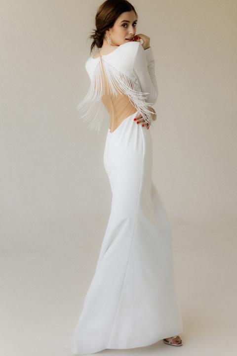 Длинное вечернее платье белого цвета со шлейфом и бахромой из бисера на спине